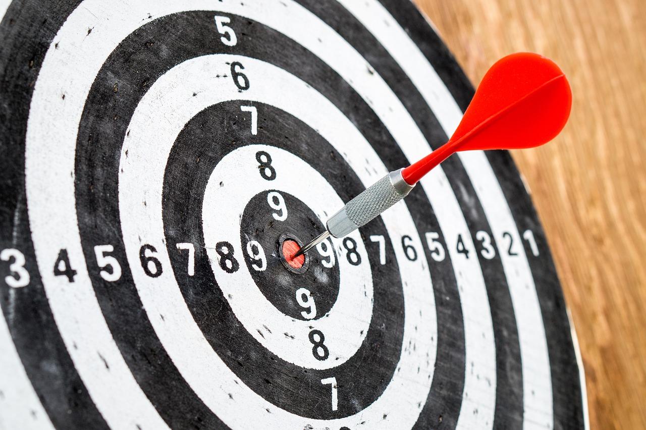 Dartboard with red dart in the bullseye