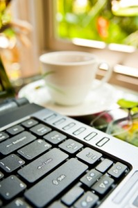 Laptop keyboard with ceramic coffee cup in the background