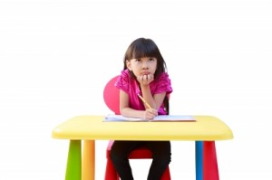 Young girl sitting at plastic desk, thinking and writing in a notebook