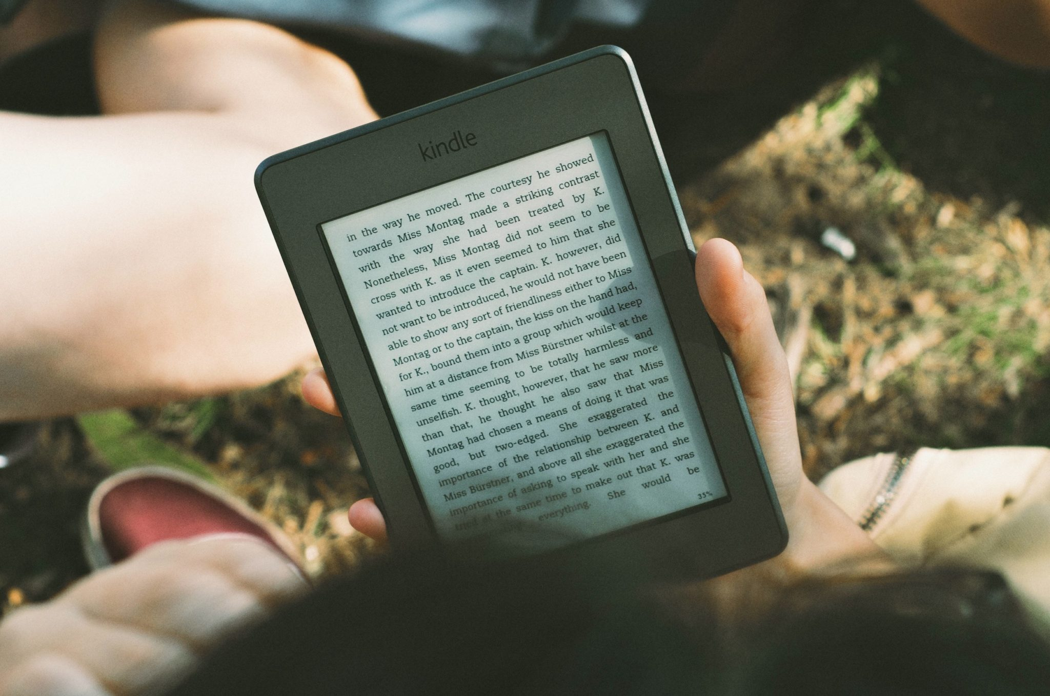 Person reading Kindle Ereader outside, by James Tarbotten on stocksnap.io