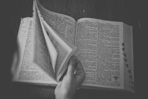 B/W photo of person leafing through dictionary by Sonja Langford from stocksnap.io