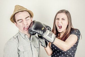 Female wearing boxing gloves hitting a man in a hat by Ryan McGuire from stocksnap.io