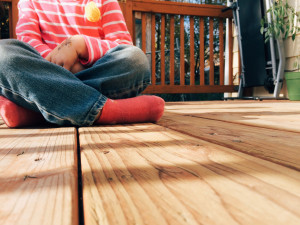 Child sitting on wooden deck by Jeri Johnson from stocksnap.io