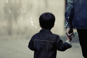 Kid with bubbles holding adult's hand by Leeroy from stocksnap.io