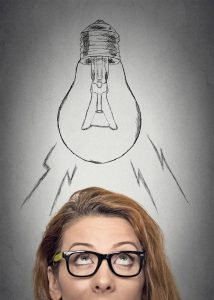 Headshot thinking businesswoman with glasses having an idea looking up with light bulb over her head isolated grey wall background. Human face expressions, emotions. Creativity concept