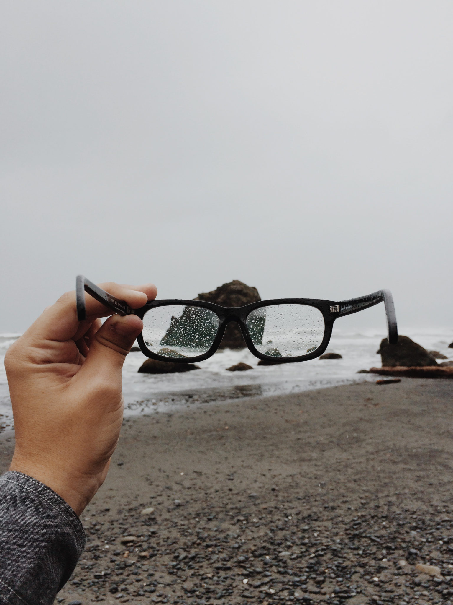 Person holding eyeglasses in the rain by Colby Schenck from stocksnap.io