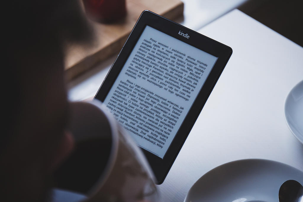 Person drinking coffee and reading Kindle by free stocks.org