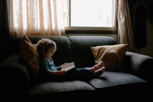 Reading child on couch by Josh Applegate from stocksnap.io