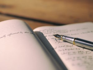 Handwritten notes in a journal by Aaron Burden from stocksnap.io