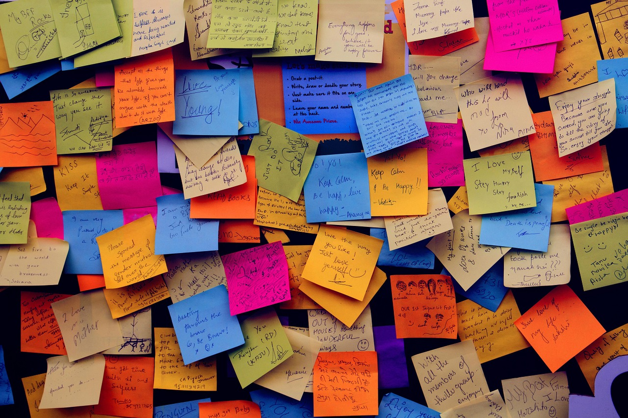 Numerous sticky notes overlapping on a wall