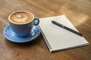 Cup of frothy coffee next to a notebook