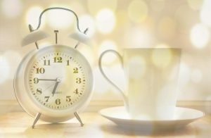 Alarm clock and mug in bright sun