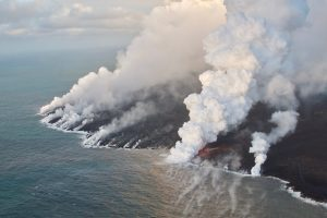 July 5, 2018 (USGS HVO, public domain) Having crusted over about 0.8 km (0.5 mi) upchannel from the ocean entry, lava oozes from the flow's molten interior to enter the sea along a broad flow front on the northern (Kapoho) side of the flow.