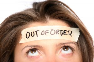 "Woman with an ""Out of Order"" sign taped to her forehead"