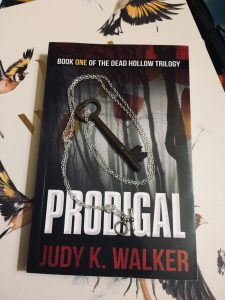 A skeleton key on a chain, resting on a copy of Prodigal, by Judy K. Walker