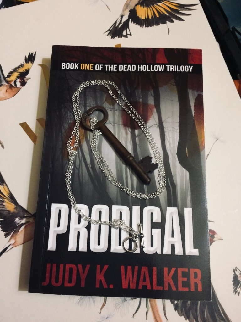A skeleton key on a chain, resting on a copy of Prodigal, by Judy K. Walker