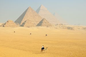 A figure on a camel with Egyptian pyramids in the distance