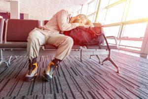 Man sleeping, head on bag, in airport