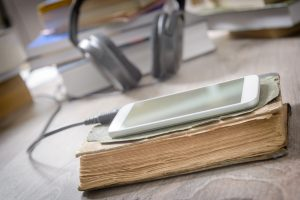 Smart phone with headphones and the paper books. Concept of listening to audiobooks.